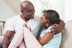 放松在长沙发的愉快的夫妇 免版税库存照片