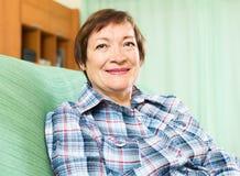 放松在长沙发的愉快的资深妇女画象  免版税库存照片