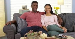 放松在长沙发的愉快的年轻黑夫妇看照相机 免版税库存照片