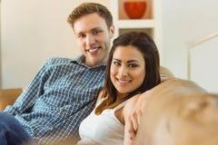 放松在长沙发的愉快的年轻夫妇 免版税库存照片