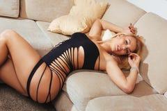 放松在长沙发的美丽的白肤金发的妇女画象  免版税图库摄影
