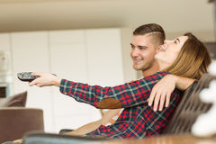 放松在长沙发的逗人喜爱的夫妇看电视 免版税图库摄影