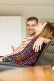 放松在长沙发的逗人喜爱的夫妇看电视 图库摄影