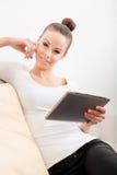 放松在长沙发的逗人喜爱的少妇 免版税库存照片