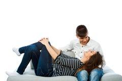 放松在长沙发的青少年的夫妇。 免版税库存照片