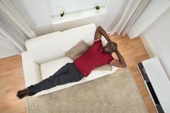 放松在长沙发的非洲年轻人 库存图片