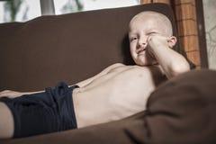放松在长沙发,青少年正面放置的男孩懒惰 库存图片