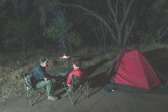 放松在露营地的成人夫妇在夜之前 冒险在国家公园,南非 灼烧的阵营火和帐篷在backgr 库存图片