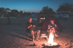 放松在露营地的成人夫妇在夜之前 冒险在国家公园,南非 灼烧的阵营火和帐篷在backgr 免版税图库摄影