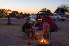 放松在露营地的成人夫妇在夜之前 冒险在国家公园,南非 灼烧的阵营火和帐篷在backgr 免版税库存照片