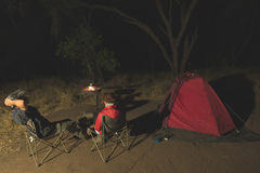 放松在露营地的成人夫妇在夜之前 冒险在国家公园,南非 灼烧的阵营火和帐篷在backgr 免版税库存图片