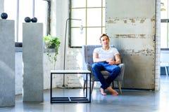 放松在顶楼样式apar的一把扶手椅子的一个年轻英俊的人 免版税库存图片
