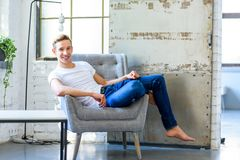 放松在顶楼样式apar的一把扶手椅子的一个年轻英俊的人 免版税库存照片
