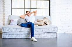 放松在顶楼样式apartm的沙发的一个年轻英俊的人 免版税图库摄影