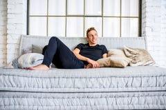 放松在顶楼样式apartm的沙发的一个年轻英俊的人 库存图片