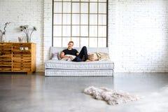 放松在顶楼样式apartm的沙发的一个年轻英俊的人 免版税库存图片