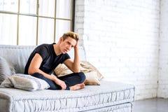 放松在顶楼样式apartm的沙发的一个年轻英俊的人 免版税库存照片