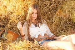 放松在领域的秸杆的秀丽妇女 免版税库存照片