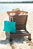 放松在轻便折叠躺椅的妇女 图库摄影