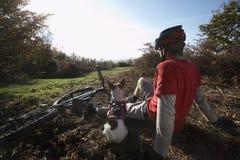 放松在登山车旁边的人和狗在乡下 免版税图库摄影