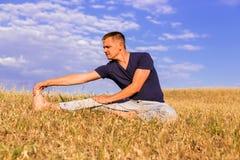 放松在晴朗的草甸的年轻人 免版税库存图片