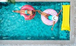 放松在水池的可膨胀的圆环的人们 免版税库存照片