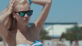 放松在水池附近的比基尼泳装的性感的女孩 股票视频