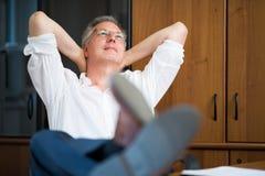 放松在他的办公室的人在工作以后 免版税库存图片