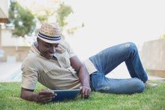 放松在他的庭院里的微笑的人使用片剂个人计算机 库存图片