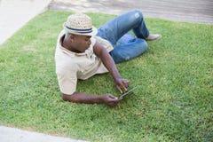 放松在他的庭院里的微笑的人使用片剂个人计算机 库存照片