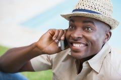 放松在他的庭院里的愉快的人谈话在电话 免版税库存图片