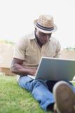 放松在他的庭院里的英俊的人使用膝上型计算机 库存图片