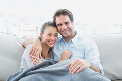 放松在他们的沙发的快乐的夫妇微笑对照相机在毯子下 免版税库存图片