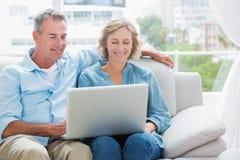 放松在他们的长沙发的快乐的夫妇使用膝上型计算机 库存图片