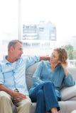 放松在他们的长沙发的快乐的夫妇有闲谈 免版税库存照片