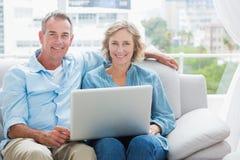 放松在他们的长沙发的愉快的夫妇使用膝上型计算机 免版税库存图片