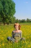 放松在黄色开花的草甸的人 库存照片
