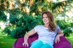 放松在绿草的一把辎重袋椅子的女孩 库存照片