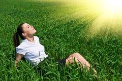 放松在绿草领域室外下面太阳的女商人 美丽的女孩在休息的衣服,春天风景,增殖比穿戴了 库存图片