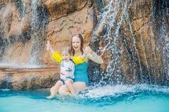 放松在aquapark的瀑布下的母亲和儿子 库存照片