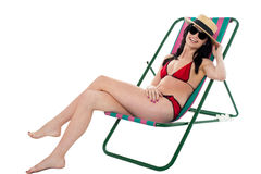 放松在deckchair的年轻比基尼泳装妇女 免版税库存照片