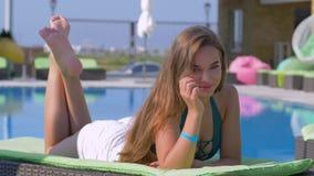 放松在sunbed的一好日子的长发愉快的女性由蓝色水池在手段在夏天休假期间 股票录像