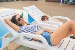放松在sunbed的不尽的夏天逗人喜爱的婴孩和母亲 免版税库存照片
