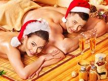放松在Xmas温泉的男人和妇女。 免版税库存图片
