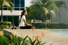 放松女商人瑜伽在办公楼之外的莲花坐 库存照片