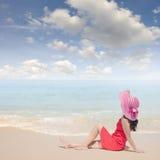 放松妇女坐海滩和蓝天 免版税库存图片