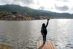 放松妇女的摄影和采取照片在夏天室外阳光的天空的湖河边 登上和家逗留背景 免版税库存图片