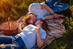 放松年轻的夫妇以后有野餐 妇女和人说谎在草和谈话在日落 变冷的人  免版税库存图片