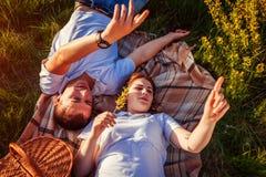 放松年轻的夫妇以后有野餐 妇女和人说谎在草和谈话在日落 指向天空的人 库存照片