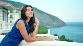 放松微笑的美丽的妇女有站立在豪华旅馆阳台或大阳台的假期  股票录像
